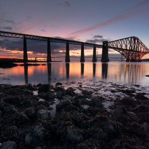 """Forth Bridge at Sunset. The Forth Bridge is one of Scotland's iconic landmarks, stretching between South and North Queensferry. The bridge first opened in 1890 and it went through a full restoration in 2012. In July 2015, UNESCO inscribed the Forth Bridge as the sixth World Heritage site in Scotland. This picture is available on Lustre Paper and Fine Art Hahnemuhle Photo Rag as well with sizes ranging from 4""""x6"""" to 24""""x36"""".The i,age is of The Forth Bridge in sunset colours. In the bottom third are rocks and pebbles leading the viewer's eyes toward the middle section where the water reflecting the bridge and the sunset colours carries the eye towards the bridge. The bridge itself runs from the top left inwards to the right. Prints available from ZenscapePhoto at www.zenscapephoto.co.uk"""