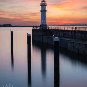 This is a photograph of Newhaven Lighthouse in Edinburgh, during sunset. This long exposure photo has vibrant colours and a well balanced composition. ZenscapePhoto Edinburgh based photographer
